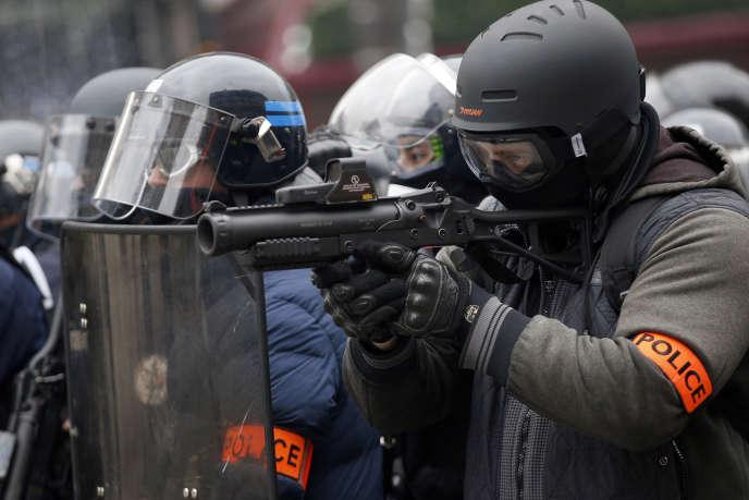 Un policier armé d'un lanceur de balle de défense, lors d'une manifestation des « gilets jaunes», sur les Champs-Elysées, le 15 janvier.