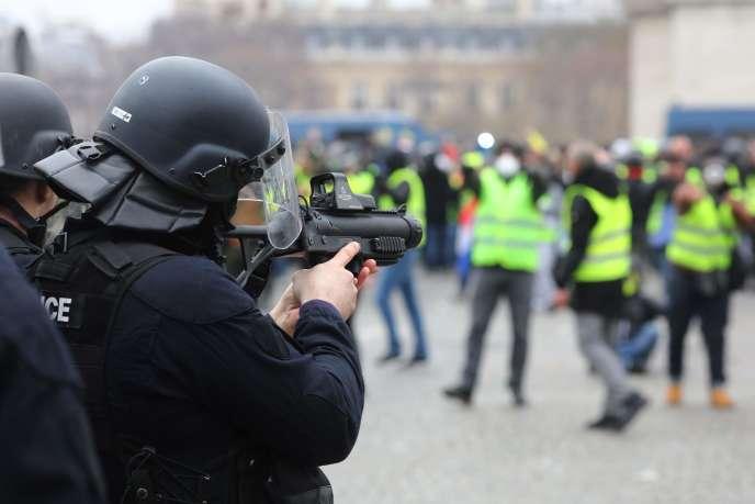 Un policierpointe son lanceur de balle de défense(LBD40)durant la manifestation des« gilets jaunes», place de l'Etoile à Paris, le 12 janvier.