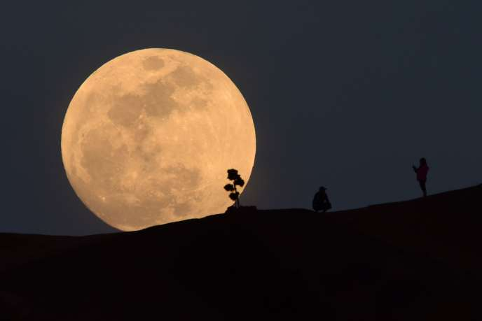 (FILES) In this file photo taken on January 30, 2018, a person poses for a photo as the moon rises over Griffith Park in Los Angeles, California. The space agencies of the United States and China are in touch and coordinating efforts on Moon exploration, NASA said on January 18, 2019, as it navigates a strict legal framework aimed at preventing technology transfer to China. / AFP / Robyn Beck