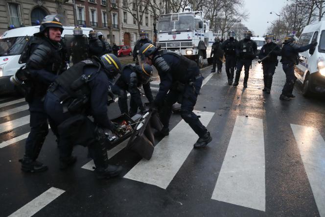 Des policiers autour d'un feu de circulation endommagé, samedi 19 janvier, à Paris.