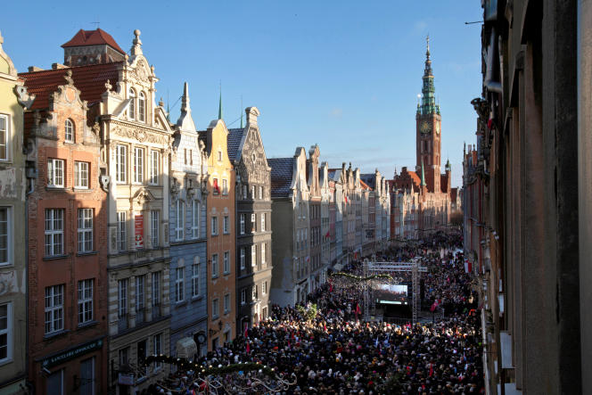 Des habitants de Gdansk regardent la retansmission des funérailles de leur maire assassiné sur un écran géant, samedi 19 janvier.