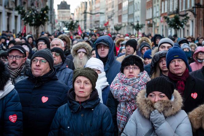 Des habitants de Gdansk regardent les funérailles de leur maire assassiné, sur un écran géant devant l'église Sainte-Marie à Gdansk, samedi 19 janvier.
