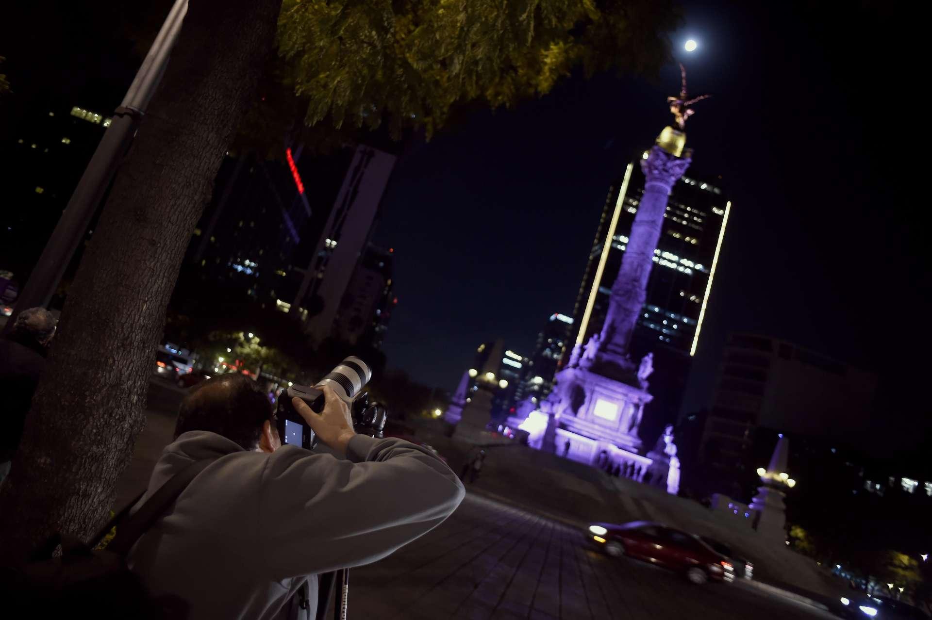 Un homme prend en photo l'éclipse devant la statue« L'Ange de l'Indépendance », à Mexico.