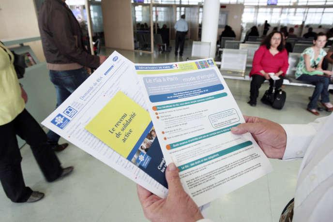 Une personne présente les brochures informant sur le RSA mises à la disposition des usagers dans un centre de la CAF à Paris.