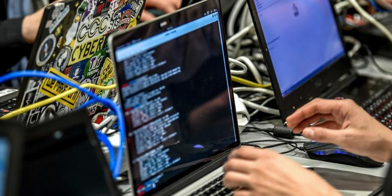 People deliver a computer payload while working on a laptop on January 22, 2019 in Lille, during the 11th International Cybersecurity Forum. The International Cybersecurity Forum will be held on January 22 and 23 in Lille. / AFP / PHILIPPE HUGUEN