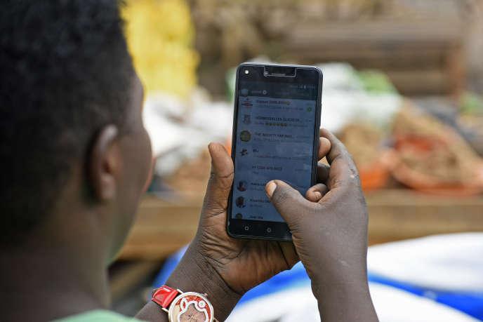 Une jeune Ougandaise naviguant sur l'application de messagerie instantanée WhatsApp, à Kampala, en juillet 2018.
