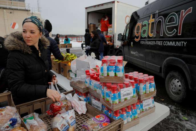 L'épouse d'un membre de la garde côtière américaine travaillant sans solde ramasse des denrées alimentaires et autres fournitures distribuées par «Gather Food Pantry», à la base de Portsmouth Harbour à New Castle, dans le New Hampshire.