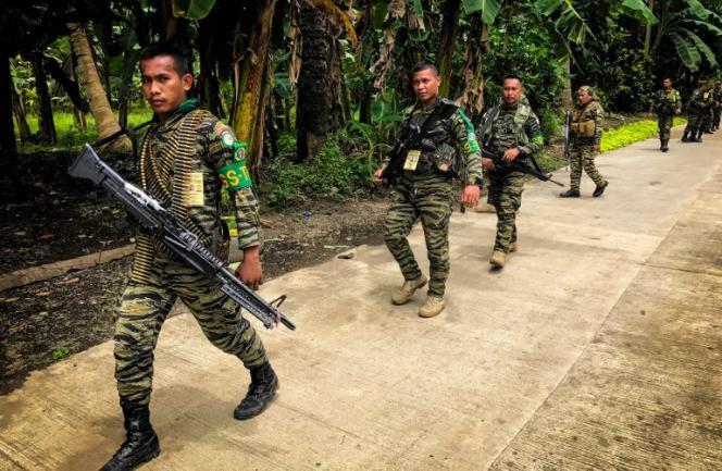 Sur cette photo, prise en août 2017, des guérilleros du Front Moro islamique de libération patrouillent sur une route de la province de Maguindanao, sur l'île de Mindanao.