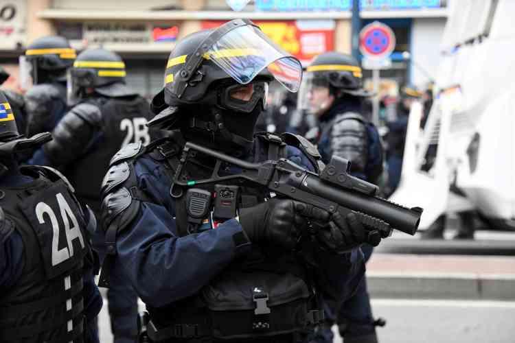 Un policier armé d'un lanceur de balles en caoutchouc et d'une « caméra piéton» lors du défilé des « gilets jaunes» à Toulouse.