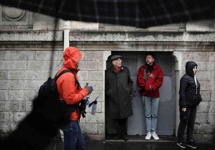 Des participants à la «Marche républicaine des libertés»s'abritent de la pluie, le 27 janvier à Paris.