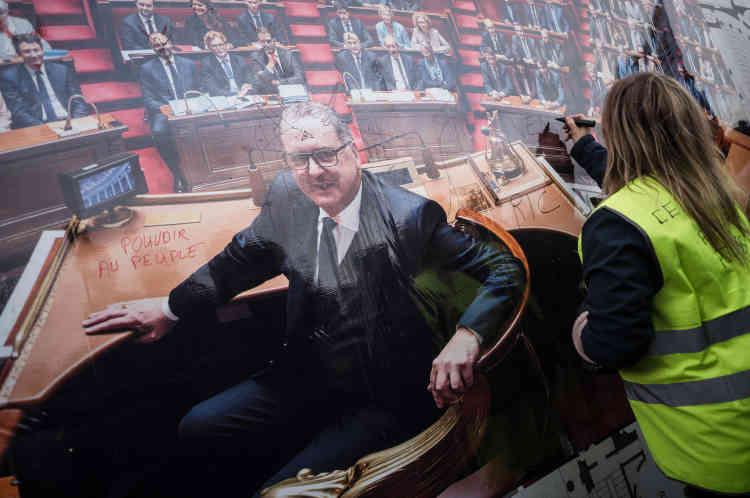 Une manifestante écrit sur une photo représentant le président de l'Assemblée nationale, Richard Ferrand, au passage des« gilets jaunes» devant la Chambre des députés.