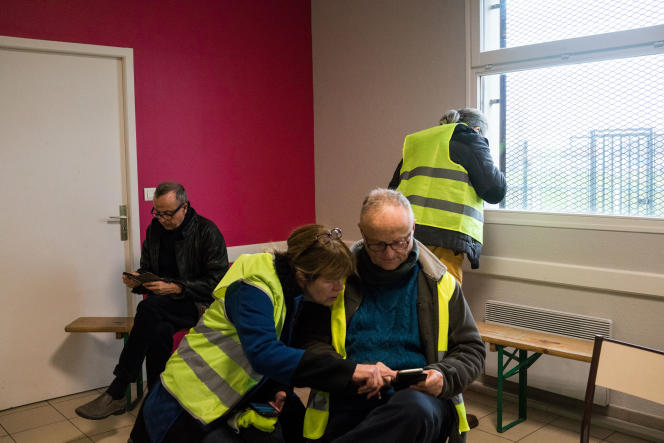 Des« gilets jaunes» consultent leurs téléphones portables à Commercy (Meuse), le 26 janvier.