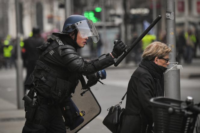 Un gendarme fait signe à une dame de s'éloigner en tenant un « tonfa», ou bâton de défense à poignée latérale, à Nantes, le 12 janvier.