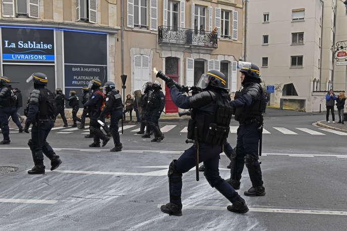 Des officiers d'une compagnie républicaine de sécurité (CRS) utilisent un lanceur Cougar pour tirer une grenade de gaz lacrymogène, à Paris, le 12 janvier 2019.