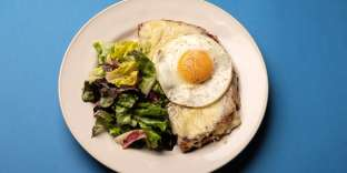 Poser le sandwich grillé sur une assiette, le couper en deux dans la diagonale, ajouter l'œuf par-dessus et servir avec une salade verte bien assaisonnée.