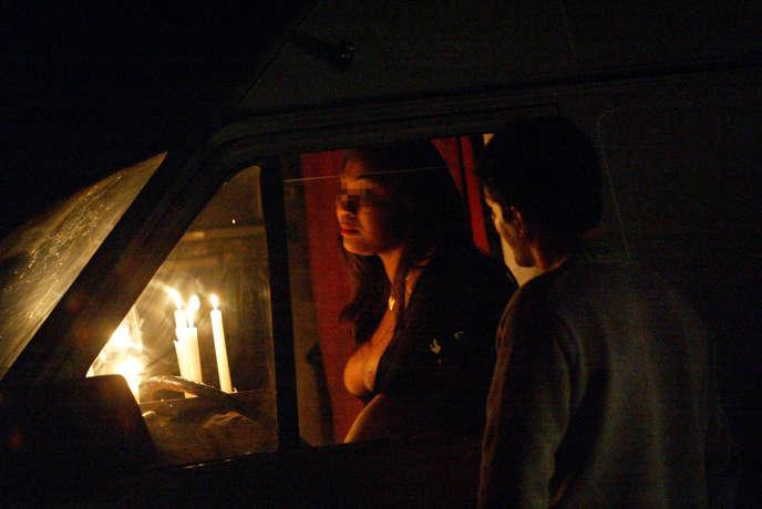 Une prostituée discute avec un client potentiel à travers la vitre de sacamionnette dans le bois de Vincennes, en octobre 2002.