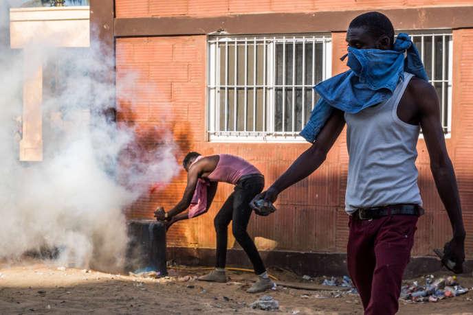 Un manifestant ramasse une pierre tandis que son camarade recouvre d'une poubelle une grenade lacrymogène lancée par la police, lors d'une manifestation à l'université Cheikh Anta Diop de Dakar, au Sénégal, le 25 janvier 2019.