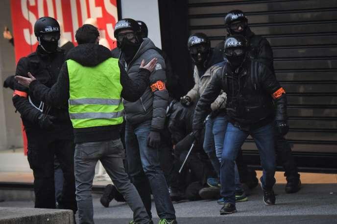 Un« gilet jaune» face aux policiers de la BAC lors de l'interpellation d'un manifestant, à Paris, le 12 janvier.