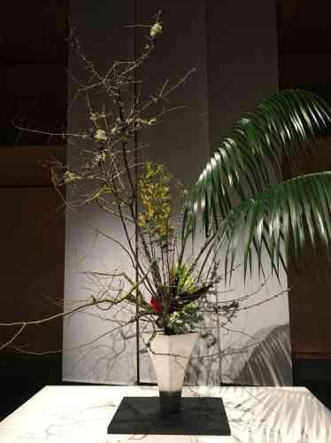 Les différents éléments de la composition, de nature et de texture variées, s'harmonisent dans un jaillissement vertical en apparence désordonné, au-dessus d'un vase à la symétrie rigoureuse.