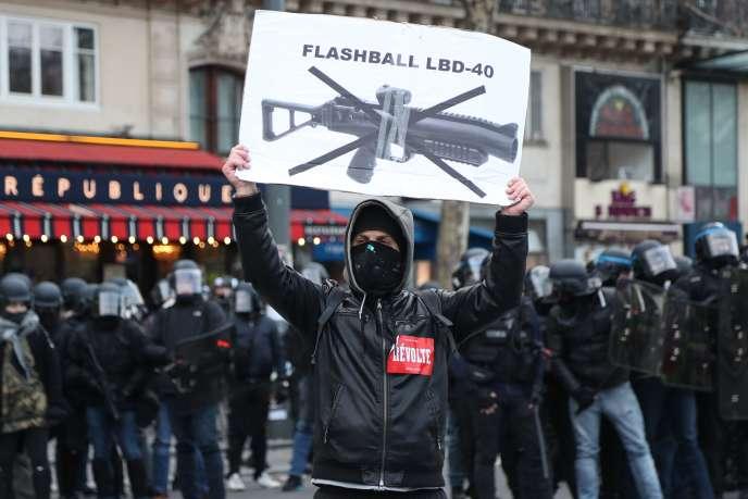 Un manifestant porte une pancarte dénonçant l'usage du lanceur de balles de défense (LBD40) lors des manifestations, pendant l'acte XII des « gilets jaunes» à Paris, samedi 2 février 2019.