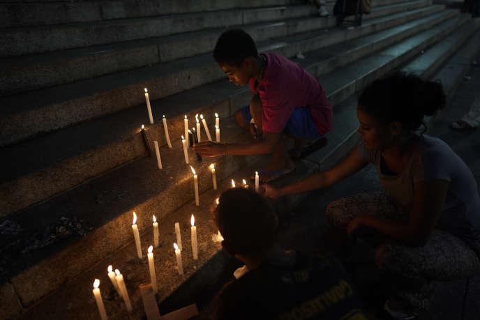 Les gens placent des bougies sur les marches de la cathédrale de Sao Paulo, au Brésil, le vendredi 1er février 2019. Une semaine après l'effondrement d'un barrage minier dans l'Etat du Minas Gerais, des dizaines de personnes ont rendu hommage aux victimes de cette tragédie.