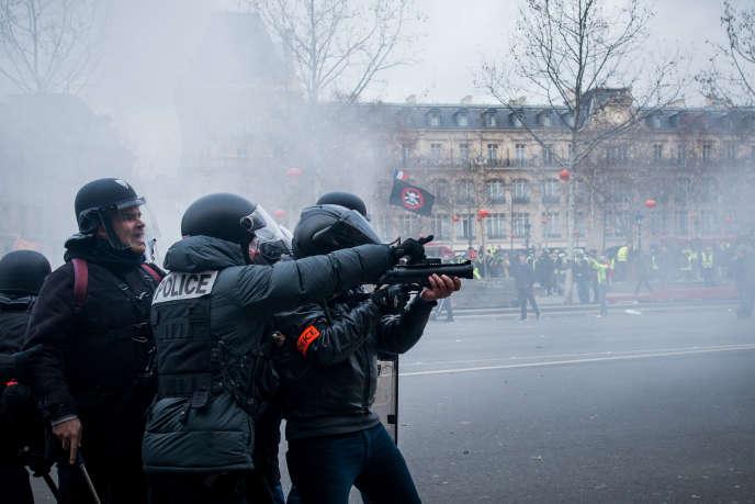 Un policier met en joue des manifestants avec un lanceur de balles de défense, le2février à Paris.