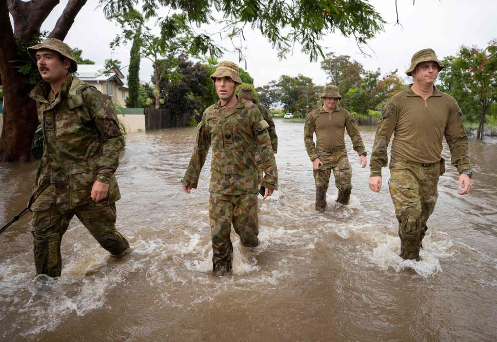 Des militaires patrouillent le 2 février dans les rues inondées de Townsville, troisième ville la plus peuplée de l'Etat du Queensland, en Australie, pour venir en aide aux habitants.
