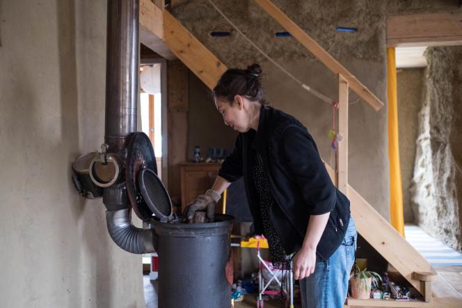 Amélie Bourquard ajoute du bois dans le poêle qui chauffe sa maison, en janvier 2019. Originaire de Reims, elle et sa famille ont décidé de changer radicalement de vie et de construire une maison au plus près de la nature, à Saint-Sève (Gironde).