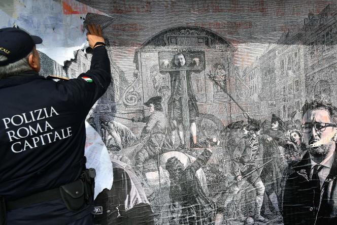 Un policier romain détruit une affiche représentant Cesare Battisti au pilori et le ministre de la justice italien, Alfonso Bonafede.