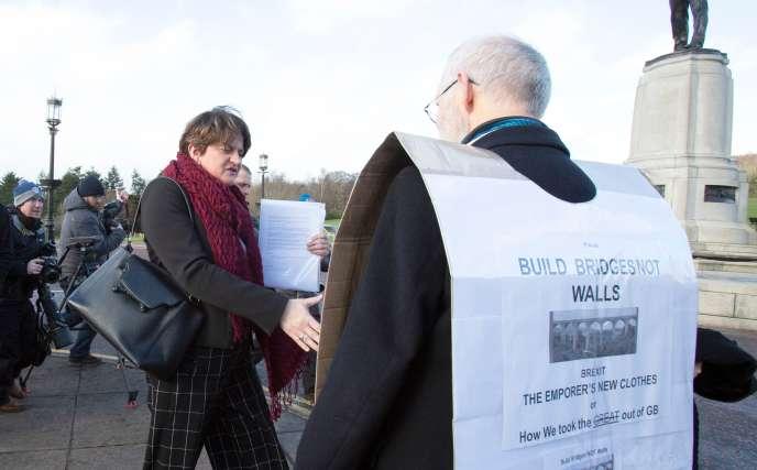 Le 6 février 2019, Arlene Foster, dirigeante du Parti syndicaliste démocrate (DUP), a accueilli un manifestant devant les bâtiments gouvernementaux du domaine Stormont à Belfast, en Irlande du Nord, après une réunion avec le Premier ministre britannique Theresa May pour des entretiens sur le Brexit. Le 5 février, en Irlande du Nord, la première ministre britannique Theresa May a promis de rechercher une solution qui maintiendrait la frontière irlandaise ouverte et préserverait l'accord de paix qui mettait fin à des années de violence sectaire dans la province britannique. Elle a passé une deuxième journée en Irlande du Nord pour organiser des réunions au Brexit avant son déplacement à Bruxelles le 7 février pour rencontrer les dirigeants européens, alors que les deux parties cherchent à sauver leur accord sur le Brexit.