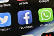 FILE - In this Thursday, Nov. 15, 2018 file photo the icons of Facebook and WhatsApp are pictured on an iPhone in Gelsenkirchen, Germany. German antitrust authorities have issued a ruling prohibiting Facebook from combining user data from different sources. (AP Photo/Martin Meissner)
