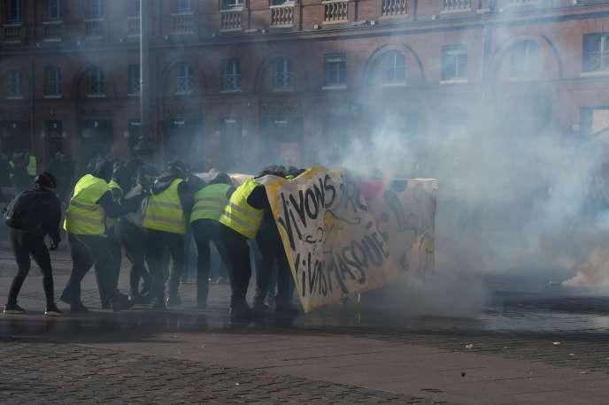 Des manifestants se protègent des gaz lacrymogènes envoyés par les forces de l'ordre derrière une banderole durant la mobilisation des« gilets jaunes» à Toulouse, le 9 février.