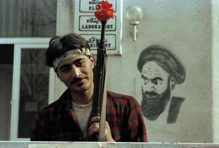 Le 15 février 1979, un soutien de l'ayatollah Khomeiny pose, une fleur au fusil, devant le siège de celui-ci à Téhéran.La République islamique est proclamée quelques semaines plus tard, le 1er avril.