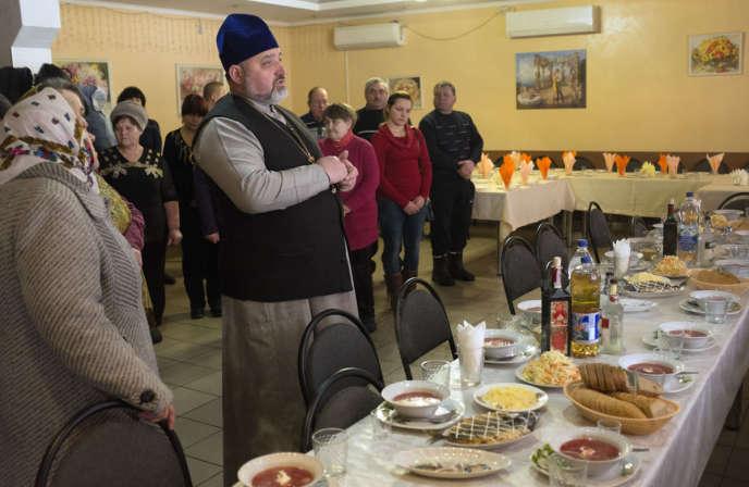 Le père Iaroslav (patriarcat de Kiev) et ses paroissiens prient avant un déjeuner commémoratif. Desna (Ukraine), le 2 février 2019.