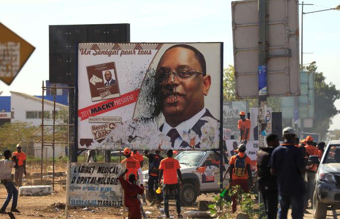 Des partisans du candidat de l'oppositon Idrissa Seck vandalisent une affiche électorale du président sortant Macky Sall, à Thiès, au Sénégal, le 3 février 2019.