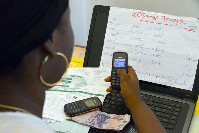 Une salariée de la société Orange Money paie une facture depuis un compte de téléphone mobile, en mai 2015, à Abidjan.