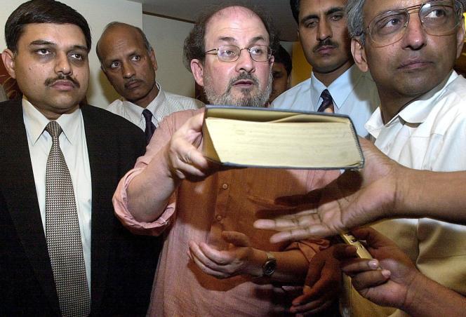 Le 16 avril 2000, Salman Rushdie, auteur des« Versets sataniques», entouré par des agents de sécurité, signe un autographe lors d'une rencontre avec la presse à New Delhi.
