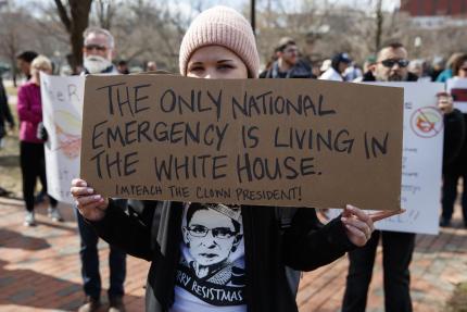 Une manifestante brandit une pancarte « La seule urgence nationale vit dans la Maison Blanche», le 18 février à Washington.
