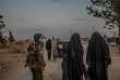 Une combattante des Forces démocratiques syriennes accompagne deux femmes de djihadistes dans le camp d'Al-Hawl, au nord-est de la Syrie, le 17 février.