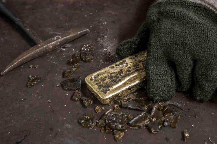 Première étape du processus de nettoyage : un ouvrier brise au marteau la couche d'impuretés au-dessus du lingot d'or obtenu après la première fonte.