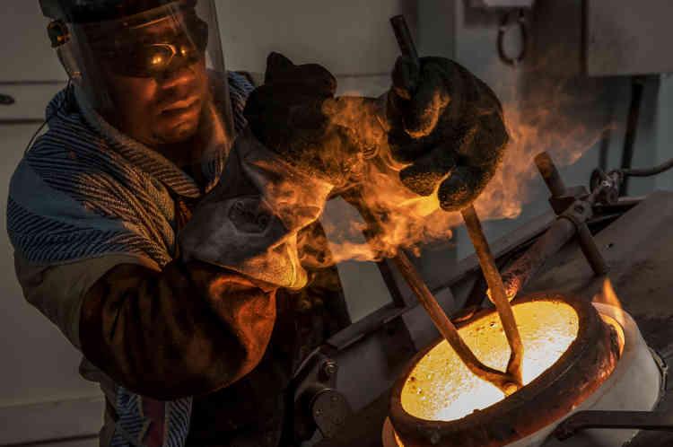 Pascal SerunjogiI, le plus ancien ouvrier de l'atelier d'AGR, effectue dans un fourneau la cuisson de la poudre d'or pur raffinée obtenue après la seconde filtration pour en avoir des granules.