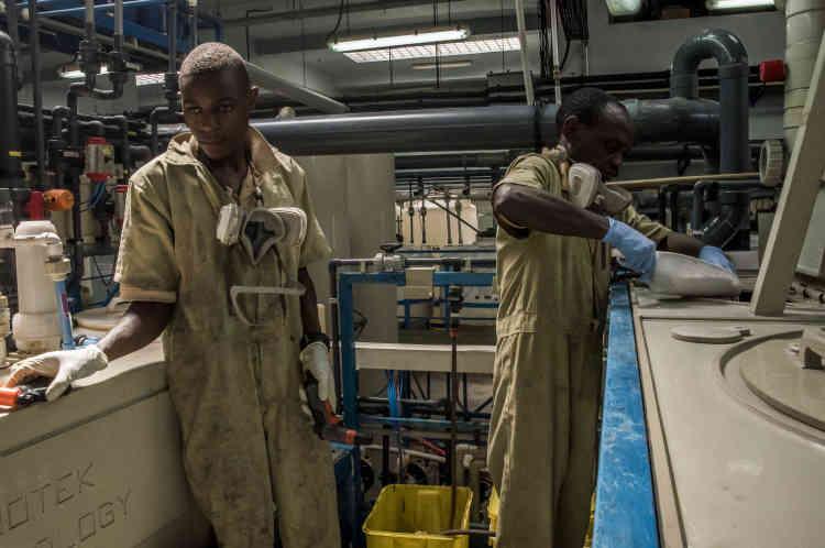 Dans la partie raffinage de l'atelier d'AGR, deux ouvriers travaillent à l'opération de la seconde filtration. Ce processus consiste à transformer l'or pur sous forme liquide.