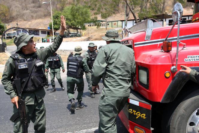 Des représentants des forces de sécurité bloquent la route où veulent passer des parlementaires de l'opposition avec leurs partisans, à proximité de Mariara, Venezuela, le 21 février 2019.