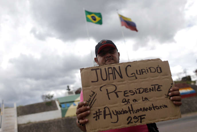 Un ressortissant vénézuélien porte une pancarte où il est inscrit :« Juan Guaido Président, oui à l'aide humanitaire», à Pacaraima, ville frontalière du Venezuela, Brésil, le 21 février 2019.
