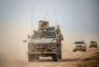 """A picture taken on February 21, 2019 shows vehicles belonging to the US-backed coalition as they drive down a road in Syria's northern Deir Ezzor province. US-backed Syrian forces tried today to negotiate the release of civilians still trapped in the Islamic State group's last redoubt, as the international coalition warned the jihadists faced """"inevitable defeat"""". / AFP / Bulent KILIC"""