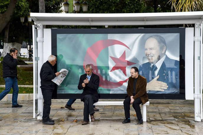 Des Algériens attendent l'arrivée du bus, à Alger, le 11 février. Derrière eux, le portrait du président Abdelaziz Bouteflika.