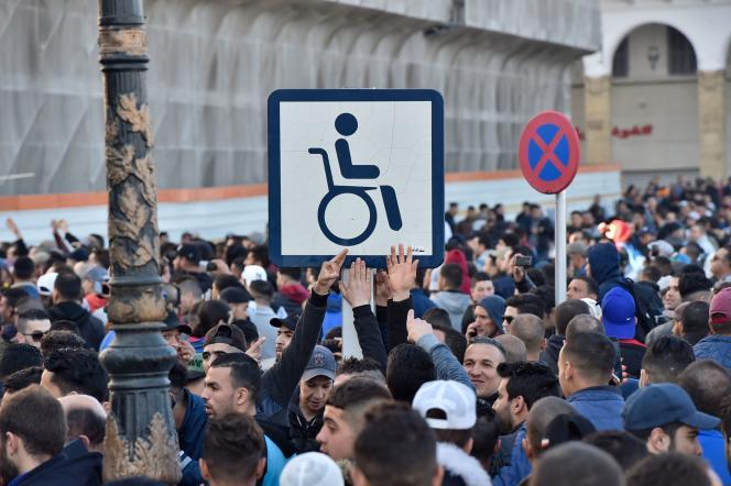 Manifestation à Alger pour protester contre le cinquième mandat du président Bouteflika, le 22 février 2019. Le panneau symbolise le président Bouteflika, qui brigue une cinquième mandat malgré son état de santé très faible et qui est« remplacé» par un cadre avec sa photo lors de cérémonies officielles.