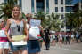 The organiser of the 'Marche des Shorts' (The March of the Shorts) Cecile Muschotti (C) holds a sign reading 'All in shorts' as she attends a rally to show support to a young woman who was attacked in a bus because she wearing shorts, in Toulon, southeastern France, on June 25, 2016. (Photo by BERTRAND LANGLOIS / AFP)