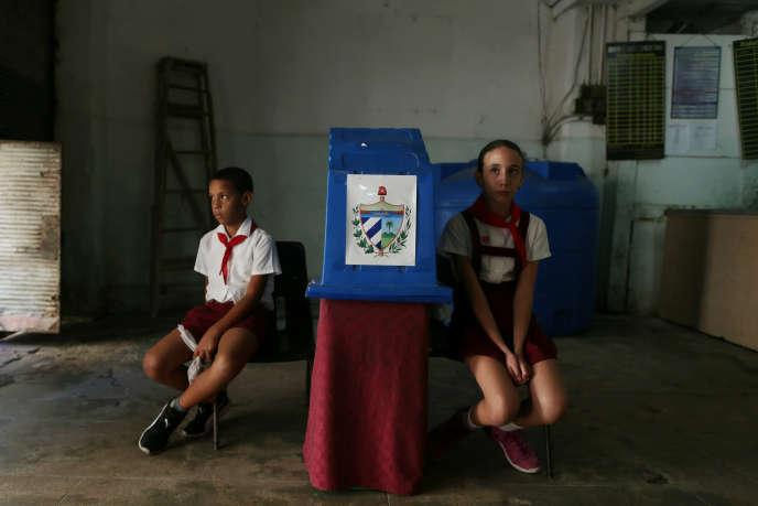 Des enfants attendent les électeurs dans un bureau de vote lors d'un référendum constitutionnel à La Havane, à Cuba, le 24 février 2019.