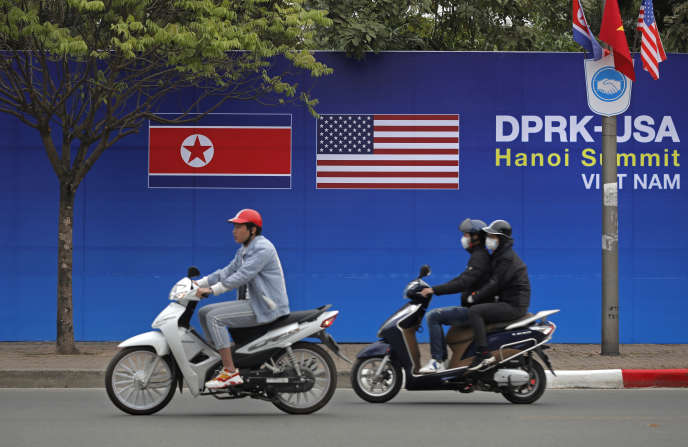 People ride motorcycles past a poster featuring the upcoming second summit between the U.S. and North Korea in Hanoi, Vietnam, Sunday, Feb. 24, 2019. The second summit between U.S President Donald Trump and North Korean leader Kim Jong Un will take place in Hanoi on Feb. 27 and 28. (AP Photo/Vincent Yu)